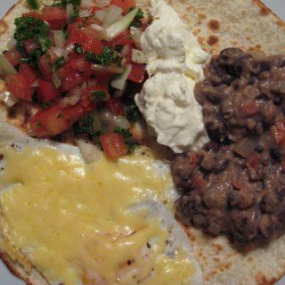 Huevos rancheros, feijões refritos, salsa, ovo e sour cream